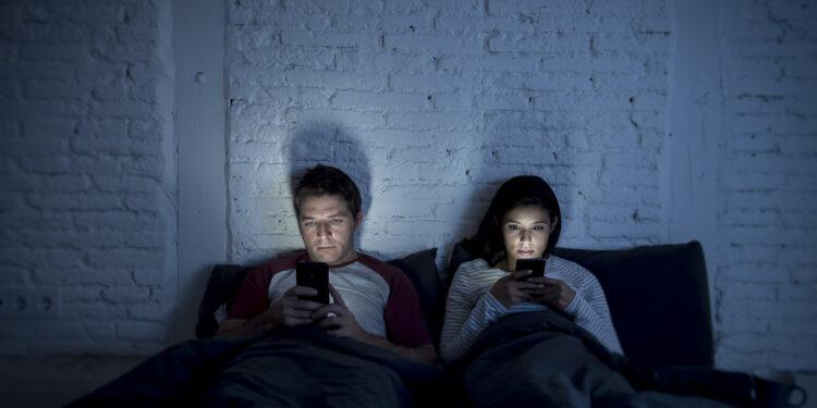 Муж и жена сидят в телефоне перед сном